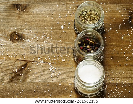 Spices: salt, pepper and herbs in small glass jar on a wooden table, top view, selective focus - stock photo