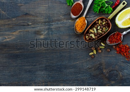 Spices selection in vintage scoop and spoons, herbs and spices over dark wooden background with space for text. Cooking ingredients. - stock photo