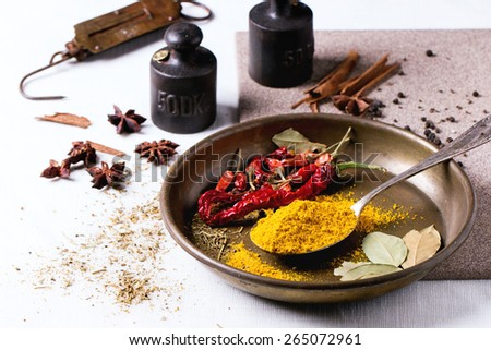 Spices turmeric and dry red hot chili peppers on metal plate, served over white tablecloth with vintage weight.  - stock photo