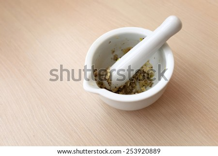 Spices with mortar and pestle on a table - stock photo