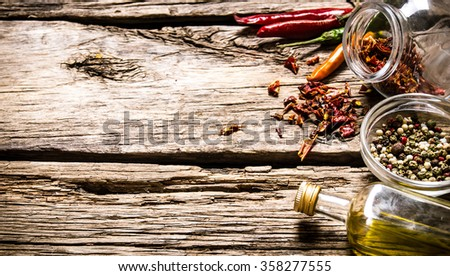 Spicy and aromatic spices with olive oil . On wooden background. Free space for text . - stock photo