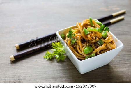 Spicy asian noodle dish with chopsticks. - stock photo