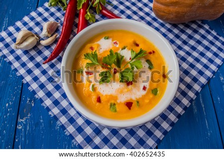 Spicy Asian soup with pumpkin and cream. On a blue wooden background  - stock photo