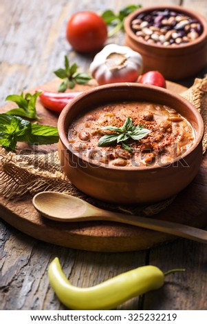 Spicy baked beans in traditional clay pot. - stock photo