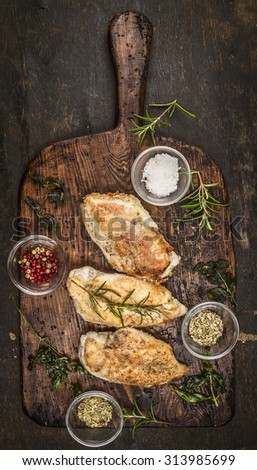 Spicy baked chicken breast on rustic wooden gutting board, top view - stock photo