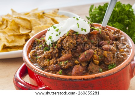 Spicy Beef and bean mexican chili with nacho chips and sour cream - stock photo