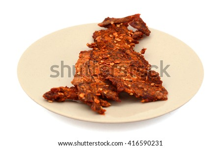 spicy beef jerky on plate isolated on white