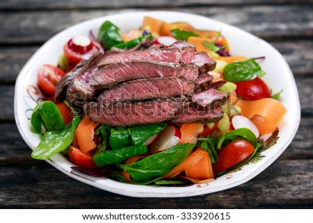 Spicy Beef Meat Salad with Carrots, Tomatoes, Cucumber, Parsley and Salad leaves Spinach, rocket, red ruby chard on old wooden table - stock photo