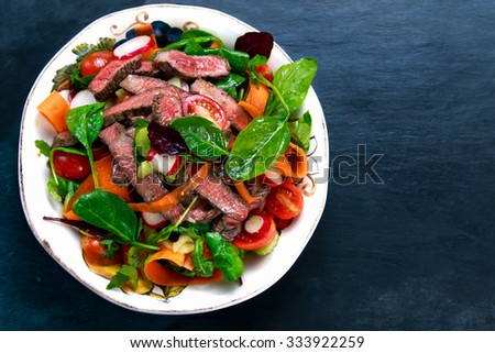 Spicy Beef Meat Salad with Carrots, Tomatoes, Cucumber, Parsley and Salad leaves Spinach, rocket, red ruby chard on blue stone background. - stock photo