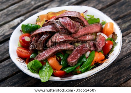 Spicy Beef Slices Meat Salad with Carrots, Tomatoes, Cucumber, Parsley, Radish and Salad leaves Spinach, rocket, red ruby chard on old wooden table - stock photo