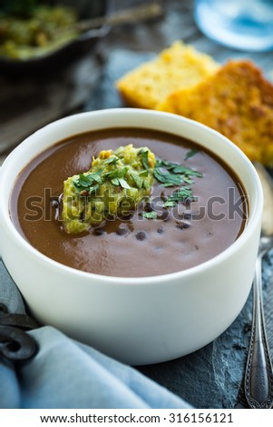 Spicy black bean soup with guacamole and corn bread - stock photo