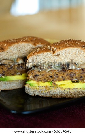 Spicy Black Bean Veggie Burger Topped with Melted Swiss Cheese, Sauteed Garlic Mushroom, and Avocado Slices on a Toasted Whole Wheat Bun - stock photo