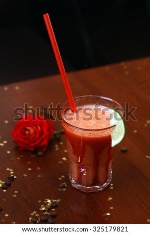 Spicy bloody mary alcoholic cocktail in glass with lime garnish with drinking straw on wooden table with coffee beans confetti and red rose, vertical photo                            - stock photo