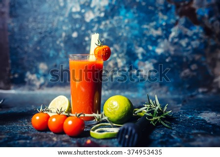 spicy Bloody Mary cocktail served on a dark bar garnished with cherry tomatoes - stock photo