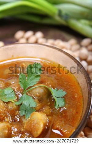 spicy chana masala, raw chickpeas around the bowlindian dish - stock photo