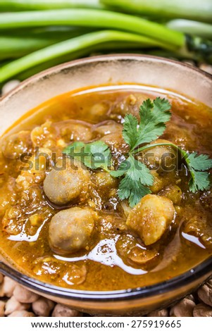 spicy chana masala, raw chickpeas around the bowl with green chilli topping, indian dish - stock photo