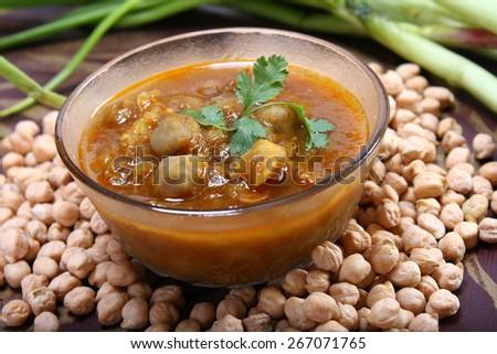 spicy chana masala, raw chickpeas around the bowl with green onionindian dish - stock photo