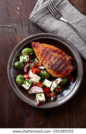 Spicy chicken breast with mediterranean-style salad - stock photo