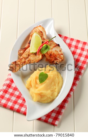 Spicy chicken drumsticks served with mashed potato - stock photo