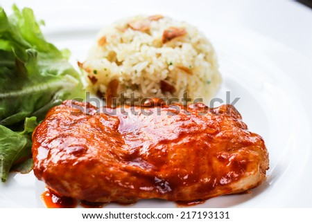 Spicy chicken steak served with mixed salad and garlic fried rice - stock photo