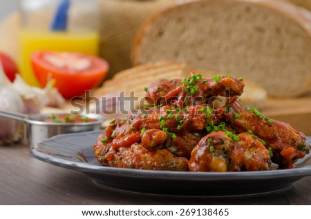 Spicy chicken wings, beer bread panini toast with garlic - stock photo
