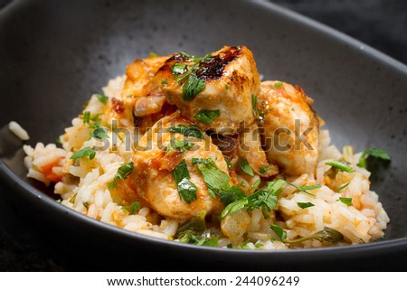 Spicy chicken with rice and parsley - stock photo