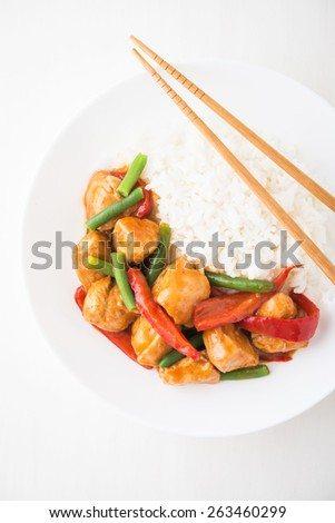 Spicy chicken with vegetables ( green beans and red pepper) and rice on white wooden background top view. Oriental food. - stock photo