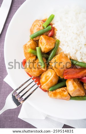 Spicy chicken with vegetables ( green beans and red pepper) and rice top view. Oriental food. - stock photo