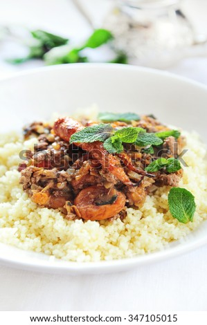 spicy couscous with lamb and dried fruits  - stock photo