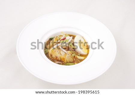 Spicy curry instant noodles soup on wooden dining table. Fresh cooked, hot with steamed smoke.  - stock photo