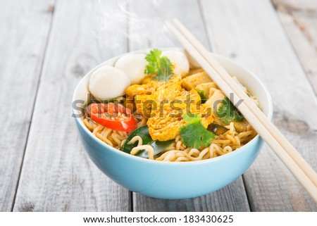 Spicy curry instant noodles soup with chopsticks on wooden dining table. Fresh cooked, hot with steamed smoke. - stock photo