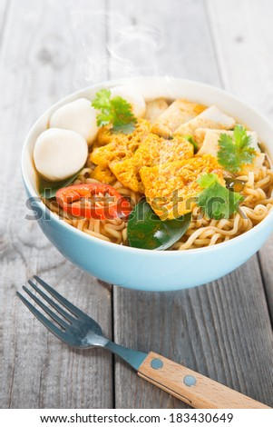 Spicy curry instant noodles soup with fork on wooden dining table. Fresh cooked, hot with steamed smoke. - stock photo