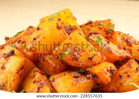 Spicy fried potatoes with herbs and spices. Shallow depth of field photograph. - stock photo