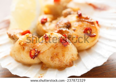 spicy fried scallops in a shell - shallow DOF - stock photo