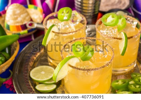 Spicy grapefruit margarita cocktail garnished with lime and jalapenos. - stock photo
