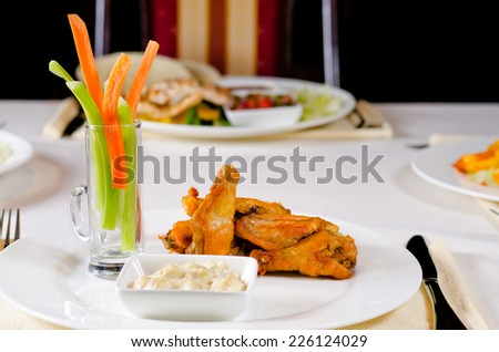 Spicy grilled chicken wings with dipping sauce and carrot and celery crudites served on a table at a restaurant - stock photo