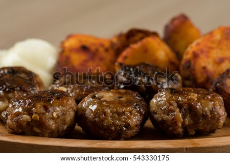 Spicy grilled meatballs with onions and tasty seasoned baked potato