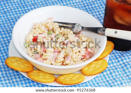 Spicy ham and pasta salad with crackers and glass of iced tea on blue gingham place mat., - stock photo