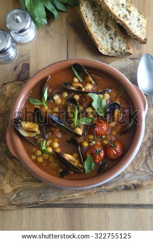 Spicy harissa mussels with tomato, chickpeas and basil - stock photo