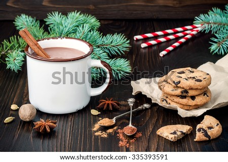 Spicy hot chocolate with cinnamon stick and chocolate chip cookies over dark wooden background. Christmas holiday drink - stock photo