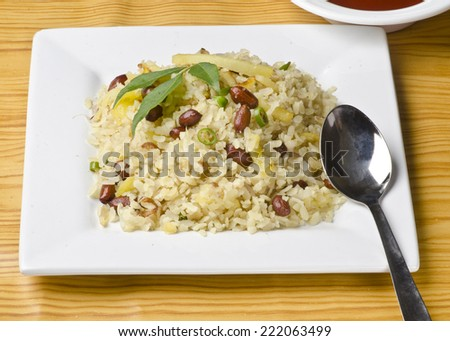 Spicy  indian breakfast called chitranna or poha with its ingredients - Peanut ,poha,potato and fresh turmeric. - stock photo