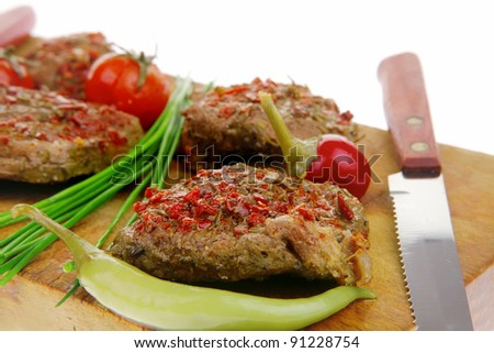 spicy meat on wood with pepper and chives