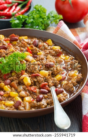 spicy Mexican dish chili con carne in a brown pottery plate, vertical