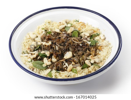 Spicy Moroccan style minced beef served with couscous mixed with chopped herbs and dried apricots, garnished with toasted cashew nuts and almond slivers and topped off with fried onions. - stock photo