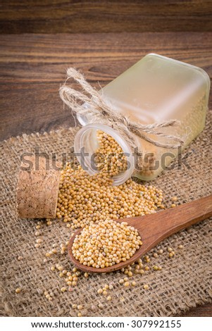 Spicy mustard seeds in a wooden background - stock photo