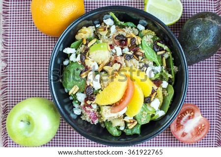 Spicy nutty fruity quinoa salad in black ceramic bowl., Homemade quinoa with spinach and fruit salad - stock photo