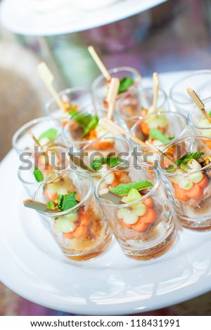 spicy pork in small shot glass with sticks as appetizer for the wedding party or business meeting - stock photo