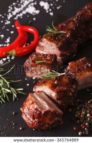 Spicy pork ribs BBQ closeup on the table with the ingredients. vertical