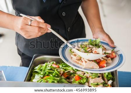 spicy pork salad, pork sausage salad, People lap spicy pork salad on a plate, Thai food. - stock photo