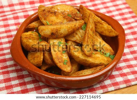 Spicy potato wedges in a terracotta dish. - stock photo